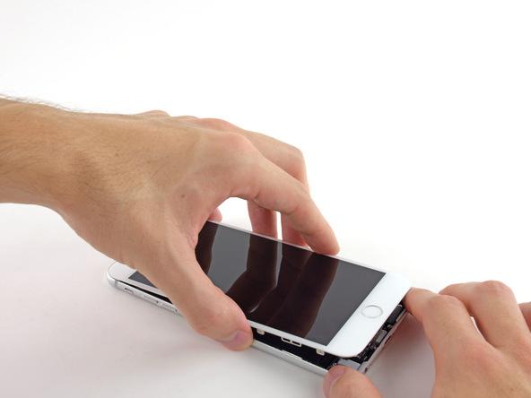 آیفون 6 پلاس تعمیری را روی میز قرار داده و درب جلو یا همان صفحه نمایش گوشی را به صورت کتابی از لبه زیرین باز کنید. به محض اینکه صفحه نمایش نسبت به درب پشت زاویه 90 درجه پیدا کرد، آن را با کش به یک جعبه یا هر ابزار دیگری که میتواند نقش تکیهگاه را ایفاء کند وصل نمایید.