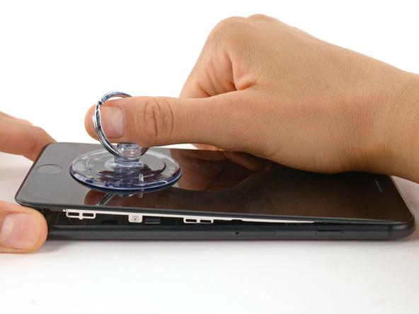 آیفون 7 پلاس تعمیری را روی میز کار قرار داده و به آرامی با دستتان پنل روی گوشی را با تمرکز نیرو بر روی لبه زیرین آن، کمی بلند کنید. در این شرایط پنل رو باید بدون هیچ مقاومتی از جانب لبه های زیرین، راست و چپ آماده جدا شدن از پنل زیر باشد. اگر در بخش هایی از این سه قسمت مقاومتی از جانبی لاستیک های آب بندی احساس کردید، با نوک اسپاتول یا پیک لاستیک آن بخش را از بین ببرید.