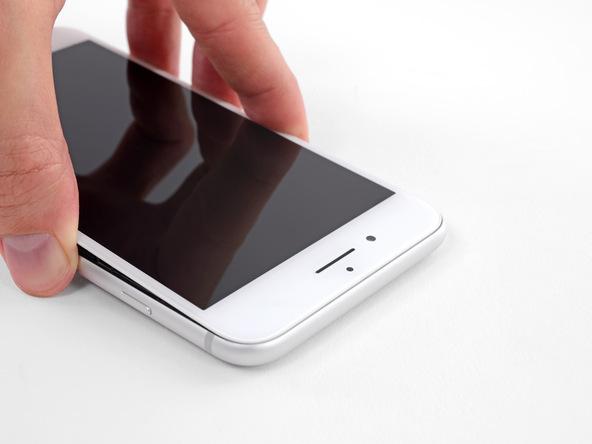 آیفون 8+ تعمیری را روی میز کار قرار دهید و صفحه نمایش آن را خیلی آرام کمی از بدنه گوشی بلند کنید. در این حالت باید لبه های نمایشگر خیلی راحت از بدنه گوشی بلند شوند. اگر بخش هایی از لبه های صفحه نمایش در برابر انجام این کار از خود مقاومت نشان دادند، با پیک این قسمت ها را شل کنید.