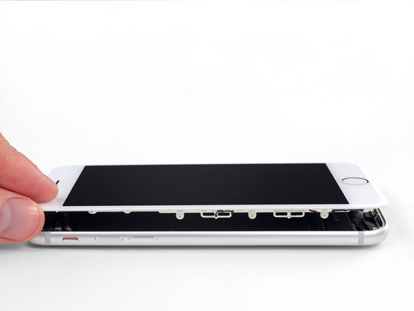 آیفون 8 را روی میز کارتان قرار داده و لبه سمت چپ صفحه نمایش آن را به صورت کتابی و مشابه با عکس دوم باز کنید. به هیچ عنوان به لبه سمت راست قاب گوشی نیروی کششی عمال نکنید. باز کردن صفحه نمایش آیفون را تا جایی ادامه دهید که نسبت به بدنه گوشی زاویه 90 درجه پیدا کند. صفحه نمایش گوشی را در همین حالت به تکیه گاهی مناسب متصل کنید. این تکیه گاه میتواند جعبه یک گوشی دیگر باشد.