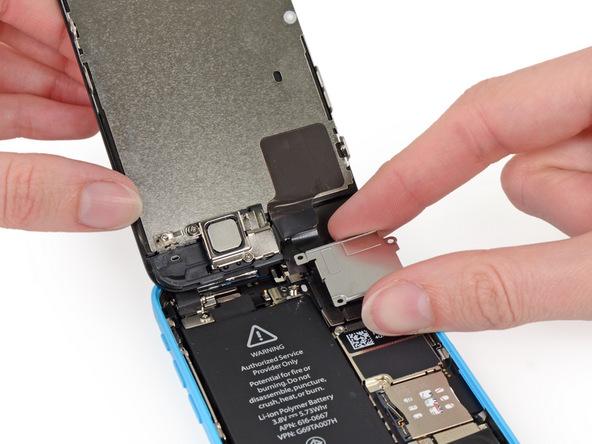 براکت گوشه سمت راست و بالای قاب پشت آیفون 5c تعمیری را از درب پشت گوشی جدا کنید.