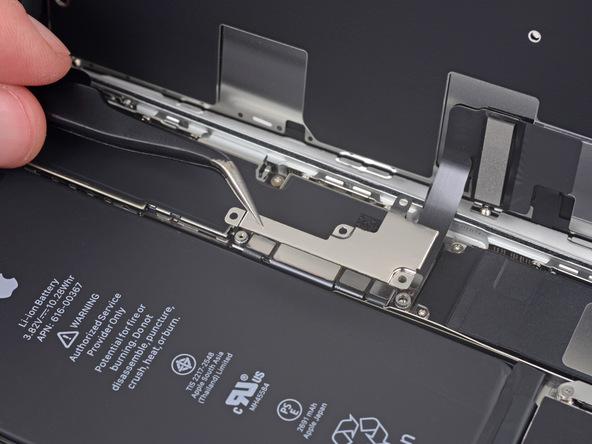 با نوک پنس براکت روی کانکتور کابل نمایشگر را از روی برد آیفون 8 پلاس تعمیری جدا کنید.
