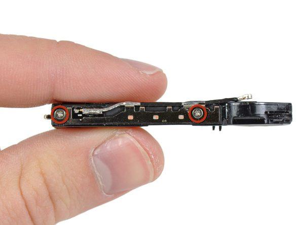 دو پیچ نگهدارنده سیم آنتن آیفون 4 اپل را از روی محفظه اسپیکر گوشی باز کنید.