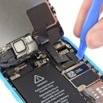 لبه قاب باز کن پلاستیکی را در گوشه سمت راست کانکتور دوربین سلفی آیفون 5C تعمیری قرار داده و آن را به سمت بالا بکشید تا از روی برد گوشی جدا شود.