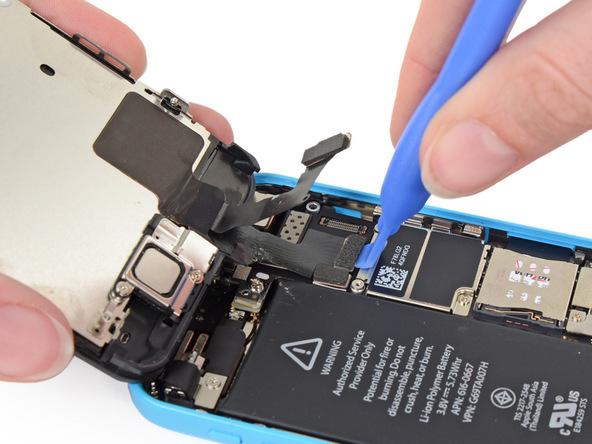 لبه قاب باز کن پلاستیکی را در زیر کانکتور ال سی دی آیفون 5 سی تعمیری قرار داده و آن را به سمت بالا هول دهید تا از روی برد گوشی جدا شود.