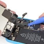لبه قاب باز کن پلاستیکی را در زیر کانکتور LCD آیفون 5C تعمیری قرار داده و آن را به سمت بالا هول دهید تا از روی برد جدا شود.