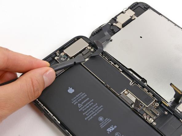 با قرار دادن نوک اسپاتول در زیر کانکتور بخش سنسورهای آیفون 7 پلاس تعمیری، مثل عکس این کانکتور را از روی برد دستگاه جدا کنید.