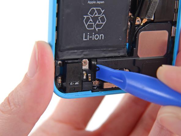 به آرامی نوک اسپاتول یا قاب باز کن را در زیر سیم سوکت دکمه هوم آیفون 5C قرار دهید و آن را از روی محفظه اسپیکر گوشی جدا کنید.