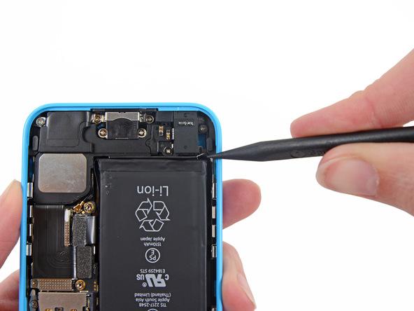 مابین لبه زیرین باتری آیفون 5C و انتهای جک هندزفری گوشی یک شکاف باریک قرار دارد. نوک اسپاتول سرگرد را دقیقا در همین بخش (شکاف مابین انتهای سوکت 3.5 میلیمتری هندزفری و لبه زیرین باتری) فرو برده و آن را به سمت دیگر شکاف هول دهید تا لبه چسب نگهدارنده باتری آیفون 5C تعمیری شل شود.