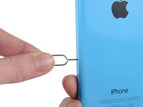 نوک سوزن باز کننده شیار سیم کارت آیفون 5C را در داخل مجرایی فرو ببرید که روی لبه سمت راست قاب گوشی واقع شده است.