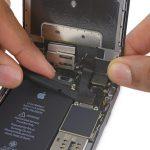 لبه پهن اسپاتول را در گوشه سمت چپ کانکتور دوربین سلفی آیفون 6 اس تعمیری قرار داده.