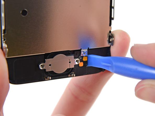 در لبه راست براکت دکمه هوم آیفون 5C یک کنتکت طلایی رنگ وجود دارد که به فلت این دکمه متصل است و جزئی از سیم آن محسوب میشود. به آرامی نوک پیک یا قاب باز کن پلاستیکی را از سمت راست به زیر این کنتکت فرو برده و آن را از روی درب جلوی گوشی آزاد کنید.