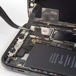 سیم سنسورهای جلوی آیفون ایکس (iPhone X) تعمیری را با نوک پنس گرفته و به آرامی سعی کنید آن را از روی برد گوشی بلند نمایید. این سیم با چسب های خاصی روی پنل پشت گوشی محکم شده است. بعد از اینکه سیم مذکور را از روی برد جدا کردید، آن را به سمت چپ بکشید تا کاملا آزاد شود.