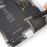 به آرامی با نوک پنس لبه اولین چسب نگهدارنده باتری آیفون 8 را باز کنید. بهتر است کار را با چسب لبه زیرین و سمت راست باتری شروع کنید.