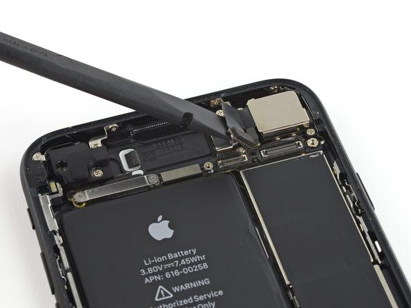 نوک اسپاتول را زیر کانکتور دوربین اصلی آیفون 7 تعمیری قرار دهید و به آن نیرویی رو به سمت بالا وارد کنید تا از روی برد جدا شود.