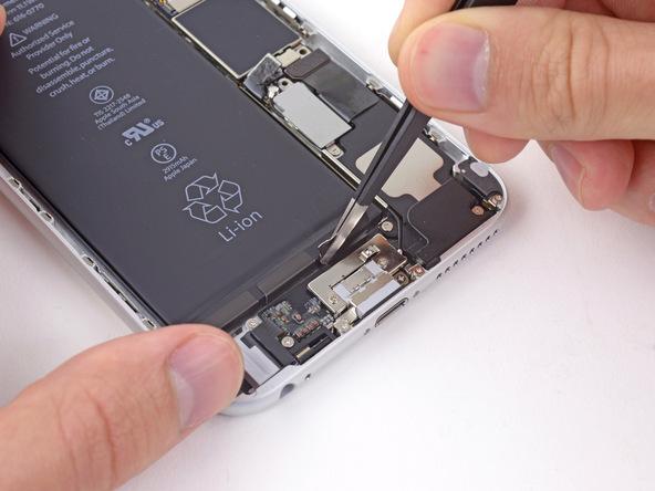 با نوک پنس لبه اولین چسب نگهدارنده باتری آیفون 6 پلاس که در لبه سمت راست باتری واقع شده را گرفته و از روی باتری جدا نمایید.