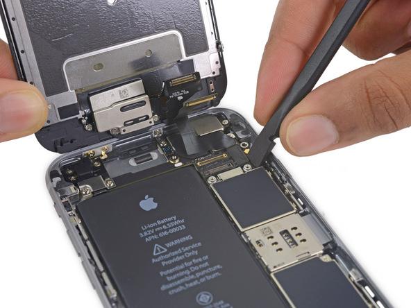 لبه پهن اسپاتول را از سمت راست در زیر کانکتور صفحه نمایش آیفون 6S تعمیری قرار داده و آن را به سمت بالا هول دهید تا از روی برد گوشی جدا شود.