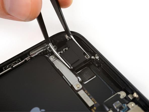آنتن وای فای آیفون 7 پلاس را پنس بگیرید و دقیقا مثل عکس کمی آن را خم کرده و به سمت بالا بکشید. سپس آنتن وای فای را به سمت خودتان بکشید تا محل قرارگیری پیچ نگهدارنده آنتن روی لبه فوقانی گوشی از جایگاه خود بلند شود.