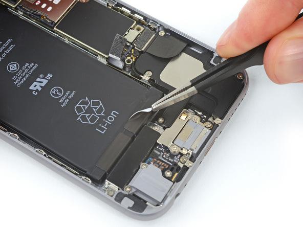 با نوک پنس لبه اولین چسب نگهدارنده باتری که در بخش زیرین و سمت راست باتری واقع شده را باز کنید.