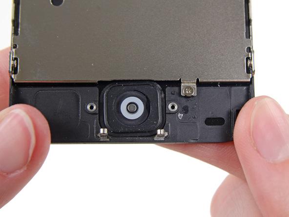 انگشت خود را به مثل عکس اول در زیر دکمه هوم آیفون 5C تعمیری قرار دهید و خیلی آرام آن را به سمت داخل هول دهید. سعی کنید این کار را به گونهای انجام دهید که فقط لبه سمت راست دکمه هوم از جایگاهش بلند شود.