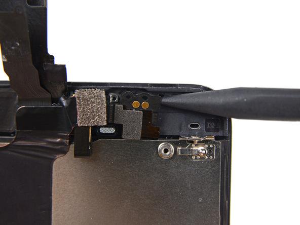 نوک اسپاتول را به آرامی در زیر کنتکت اسپیکر مکالمه آیفون 5C تعمیری قرار دهید و خیلی آرام آن را به سمت بالا بکشید تا این بخش از سیم و کنتکت اسپیکر از بدنه آیفون جدا شود.