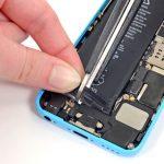 در زیر باتری آیفون 5C تعمیری دو چسب نگهدارنده بکار رفته که در لبه آن ها به هم متصل است. با قیچی یا هر ابزار مناسب دیگری وسط لبه چسب نگهدارنده باتری آیفون را ببرید تا دو چسب از هم جدا شوند.