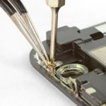 خیلی آرام با پنس کلیپس فلزی موجود در گوشه نمایشگر آیفون X تعمیری و زیر پیچی که در مرحله قبل باز کرده بودید را جدا کنید.