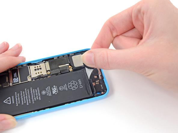 لبه اولین چسب نگهدارنده باتری آیفون 5C تعمیری را با انگشت بگیرید و خیلی آرام با نیروی یکنواخت و زاویه 60 درجه آن را به سمت عقب بکشید. دقت کنید که نیروی کششی اعمالی باید یکنواخت باشد. در این شرایط چسب نگهدارنده تقریبا چند برابر طول اصلی خود کش میآید. کشیدن چسب با نیروی یکنواخت و زاویه 60 درجه را تا جایی ادامه دهید که پاره شود.