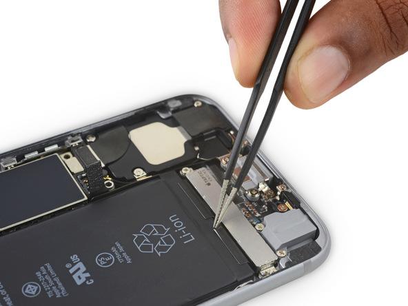 اگر دقت کنید میبینید که در لبه زیرین باتری آیفون 6 اس دو چسب کوچک به آن چسبیده شده است. به آرامی با پیک، ناخن یا نوک پنس این دو چسب را از روی باتری جدا کنید و مثل عکس آزاد نمایید.