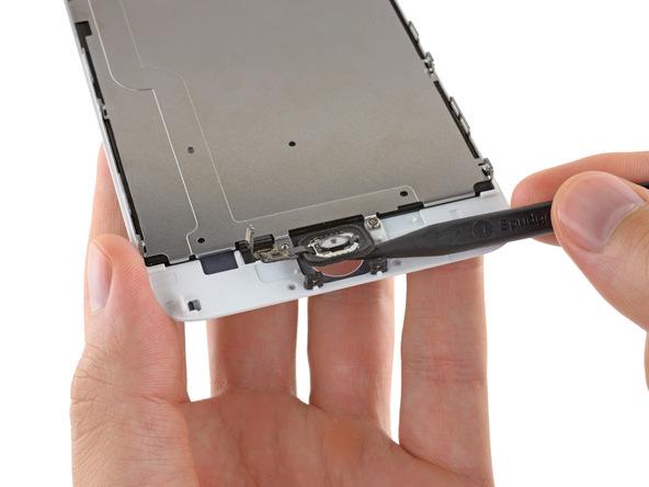 دکمه هوم آیفون 6 پلاس را با اسپاتول به سمت بالا هول دهید تا حالتی عمودی پیدا کند و لبه های سمت راست و چپ آن هم از جایگاهش بلند شوند.