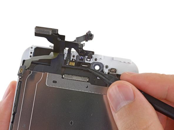 میکروفون طلایی رنگ آیفون 6 پلاس که بخشی از سیم دوربین سلفی آن است را با اسپاتول از روی درب جلوی گوشی جدا کنید.