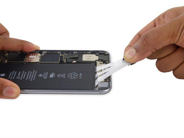 کشیدن چسب های نگهدارنده زیر باتری آیفون 6 اس پلاس را با نیروی یکنواخت ادامه دهید. در این شرایط چسب ها چند برابر طول اصلی خود کش میآیند.