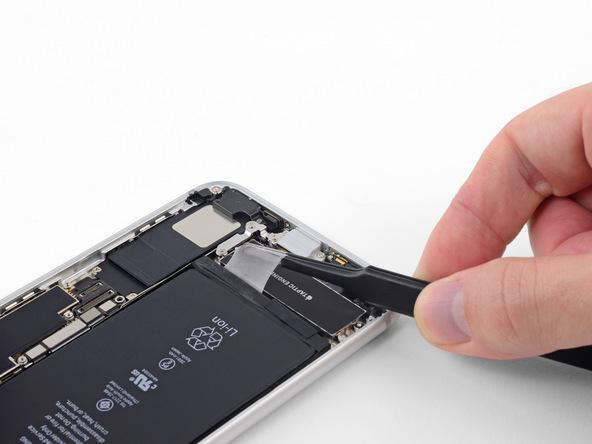 لبه اولین چسب نگهدارنده باتری را با پنس گرفته و خیلی آرام آن را به سمت عقب بکشید. سعی کنید چسب را با زاویه 60 درجه و نیروی یکسان به سمت عقب بکشید. کشیدن چسب را تا جایی ادامه دهید که چسب مذکور کاملا از زیر باتری گوشی جدا شود.