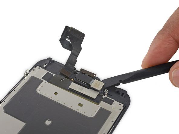 نوک اسپاتول را مثل عکس زیر لنز دوربین سلفی آیفون 6 اس تعمیری قرار داده و آن را از جایگاهش بلند کنید.