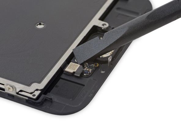 نوک اسپاتول یا پنس را در گوشه سمت راست کانکتور تاچ آیدی (دکمه هوم) آیفون 6 اس تعمیری قرار دهید.