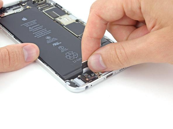 لبه سومین چسب نگهدارنده باتری آیفون 6 پلاس که در وسط واقع شده را با پنس از روی باتری باز کنید.