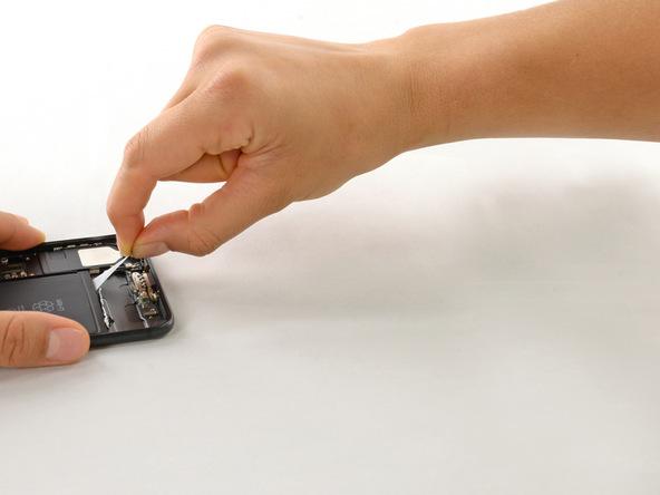 یکی از چسب های لبه باتری را با دو انگشت خود بگیرید و با نیروی یکنواخت آن را به سمت لبه زیرین گوشی بکشید. در این شرایط چسب مذکور کش خواهد آمد. کشیدن چسب با نیروی یکنواخت را ادامه دهید و سعی کنید زاویه کشش را هم حفظ کنید. این زاویه بهتر از مابین 45 الی 60 درجه باشد. کشیدن چسب را تا جایی ادامه دهید که کاملا از زیر باتری جدا شده و پاره شود.
