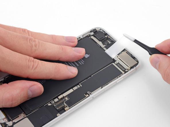 دقیقا مثل مراحل قبل سه چسب نگهدارنده باتری بعدی را هم از زیر آن باز کنید. در حین جداسازی آخرین چسب از زیر باتری حتما دست خود را روی باتری قرار داده و با نیروی کم آن را به سمت پایین فشار دهید تا ناگهان باتری از جای خود بیرون نپریده و خارج نشود.
