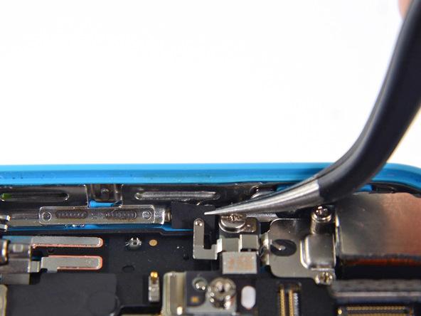 اگر روی کلیپس اتصال به پایه برد آیفون 5 سی تعمیری یک چسب کوچک قرار داده شده، آن را با نوک پنس از گوشه قاب آیفون جدا کنید.