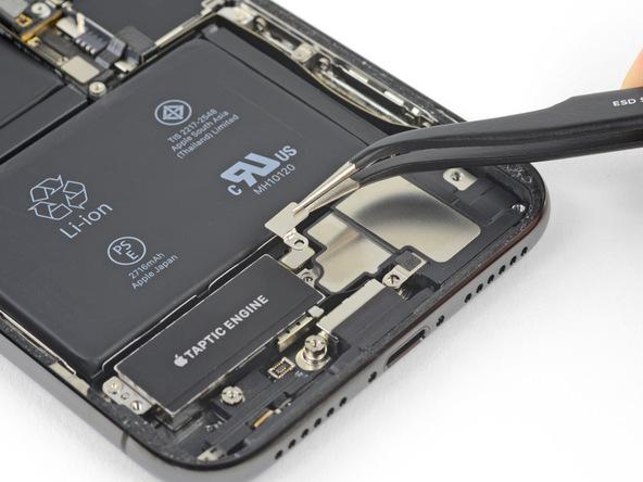 براکت روی کانکتور اسپیکر آیفون ایکس (iPhone X) تعمیری را با پنس گرفته و از روی آن جدا کنید.