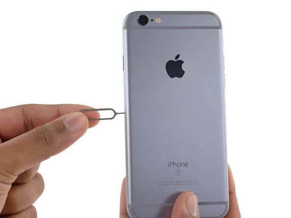 سوزن اختصاصی که برای باز کردن شیار سیم کارت آیفون 6S ارائه شده را در مجرایی فرو کنید که روی لبه سمت راست پنل پشت گوشی واقع شده است.