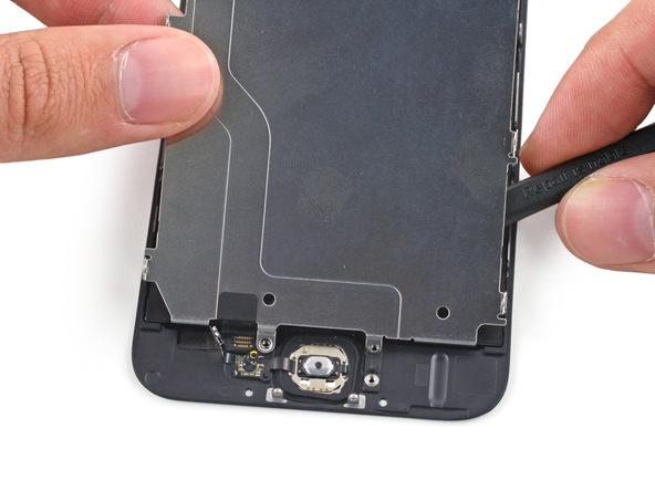 نوک اسپاتول به آرامی در زیر سوکت کانکتور دکمه هوم آیفون 6 فرو برده و آن را از روی درب پشت گوشی جدا کنید.