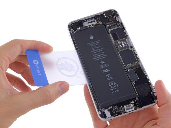 یک قاب باز کن کارتی یا هر ابزار مناسب دیگری را از گوشه سمت چپ به زیر باتری آیفون 6 پلاس تعمیری فرو برده و خیلی آرام سعی کنید آن را از درب پشت گوشی بلند نمایید.