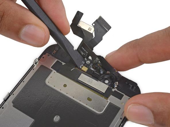 به آرامی نوک اسپاتول یا پیک را در زیر چسب میکروفون زرد رنگ آیفون 6 اس تعمیری فرو برده و آن را از روی پنل جلوی گوشی باز کنید.