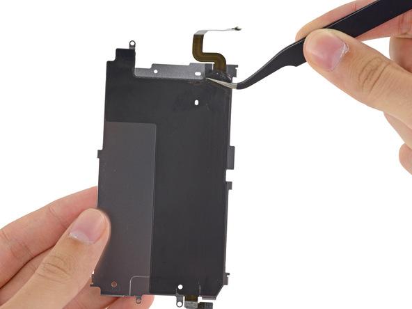 گوشه چسب روی پلیت محافظ نمایشگر آیفون 6 تعمیری را مثل عکس اول با نوک پنس گرفته و آن را از روی پیلت باز کنید تا سیم دکمه هوم آیفون نمایان شود.