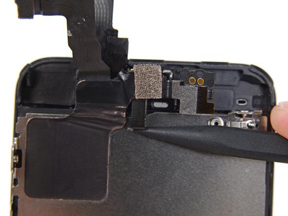 به آرامی نوک اسپاتول را در زیر کابل دوربین سلفی حرکت داده و آن را کاملا از روی درب جلوی آیفون 5 سی (iPhone 5C) جدا کنید. بخشی از میکروفون که روی این درب واقع شده را هم جدا کنید.