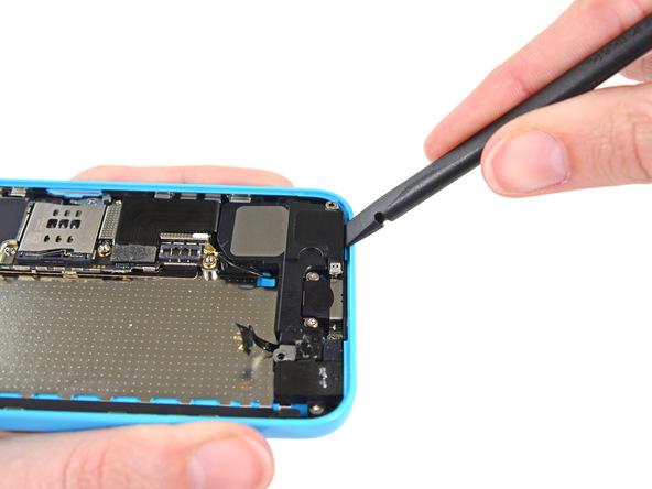 نوک اسپاتول را به آرامی مثل عکس در زیر لبه اسپیکر آیفون 5C قرار داده و آن را از روی پنل گوشی بلند کنید.