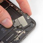 ابتدا با پنس باقی مانده های لاستیک آب بندی اسپیکر را از لبه زیرین قاب آیفون ایکس (iPhone X) جدا کنید.