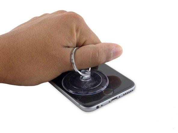 آیفون 6S تعمیری را روی میز کارتان قرار دهید. دست خود را به گونهای روی نمایشگر گوشی تکیه دهید که با یکی از انگشتانتان (عموما انگشت اشاره یا شصت) قادر به گرفتن گیره ساکشن کاپ و کشیدن آن باشید. ساکشن کاپ را با تمرکز نیرو روی لبه زیرین آیفون به سمت بالا بکشید و با انتهای دستتان بدنه گوشی را نگه دارید تا جابجا نشود. نیروی کششی اعمالی را به تدریج تا جایی افزایش دهید که در لبه زیرین قاب گوشی شکاف باریکی ایجاد شود.