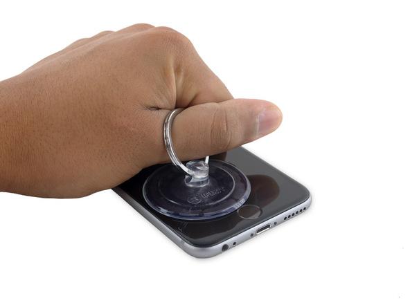آیفون 6S تعمیری را روی میز کارتان قرار دهید. دست خود را به گونهای روی صفحه نمایش گوشی بگذارید که هم از جابجا شدن آن جلوگیری کرده و هم با انگشت بتوانید گیره ساکشن کاپ را به سمت بالا بکشید. به آرامی ساکشن کاپ را با تمرکز نیرو روی لبه زیرین قاب آیفون تعمیری به سمت بالا بکشید. شدت نیروی کششی اعمالی را به تدریج افزایش دهید تا شکاف باریکی در لبه زیرین قاب آیفون 6 اس تعمیری ایجاد شود.